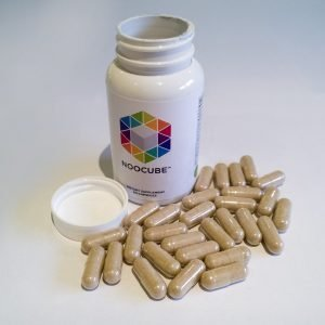Bottle of supplement with capsules outside of it