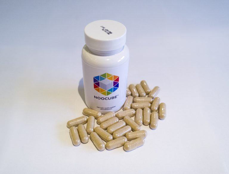 bottle of NooCube supplements with capsules around it