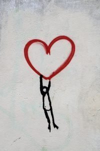 close up drawing on the wall, heart shape with man clinging on it