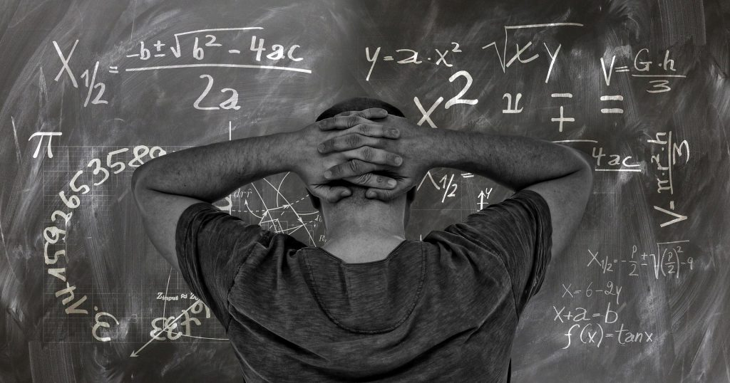 man in front of the board look at the formulas and is in a total confusion